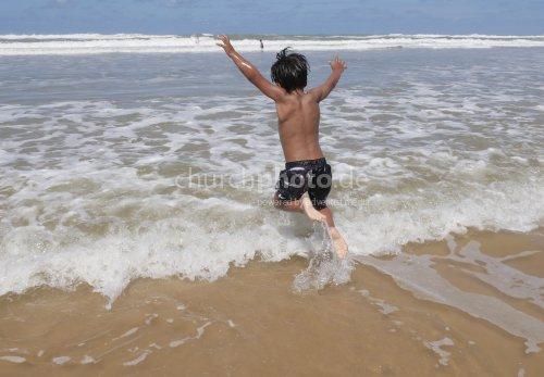 Junge springt in den Wellen
